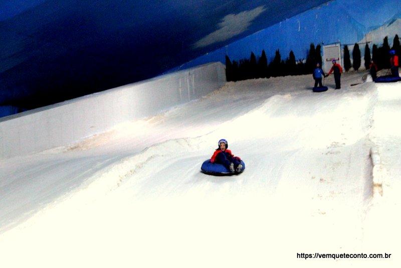 Escorregando com boia na neve no parque Snowland